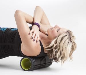Girl foam rolling her back.