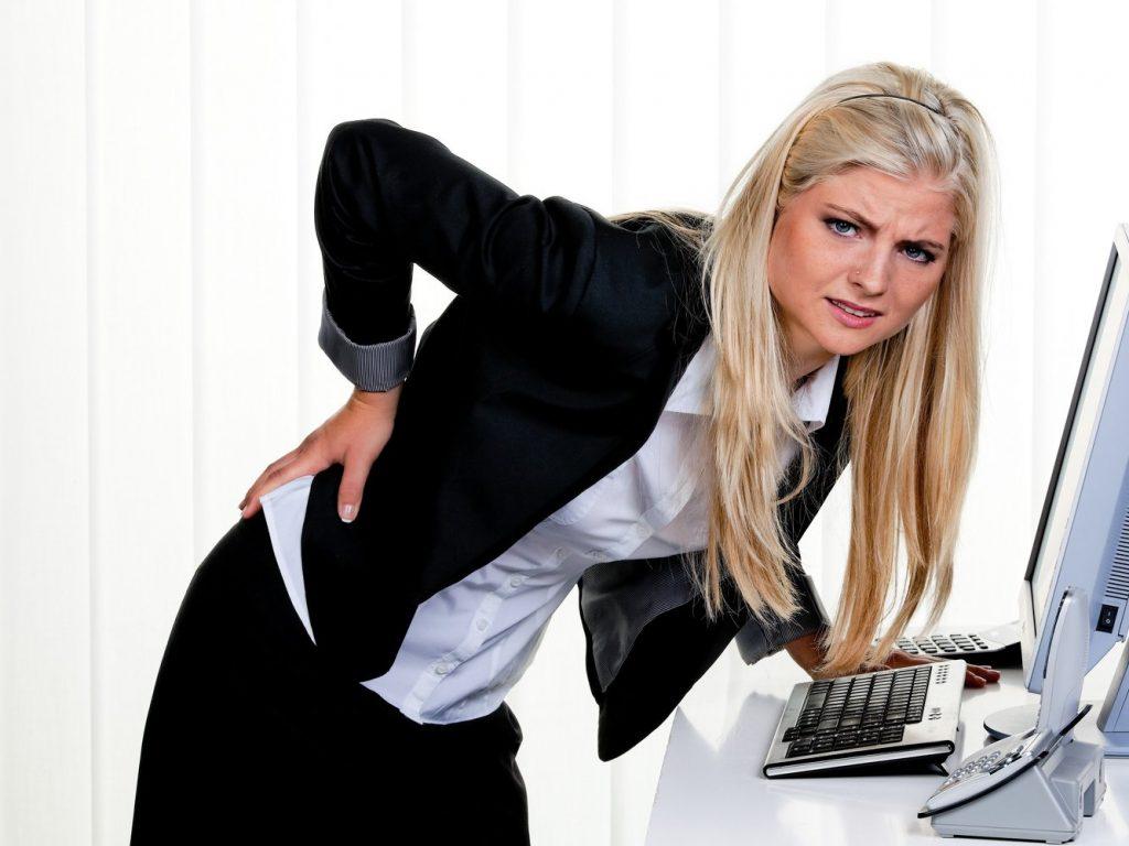 Injured Worker holding her back at computer