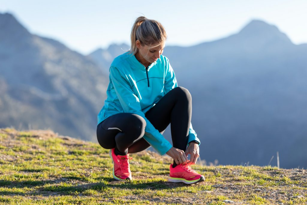 Trail runner woman tying laces on running shoes before doing workout on mountains.
