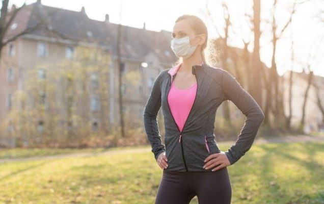 Woman with face mask standing in park.