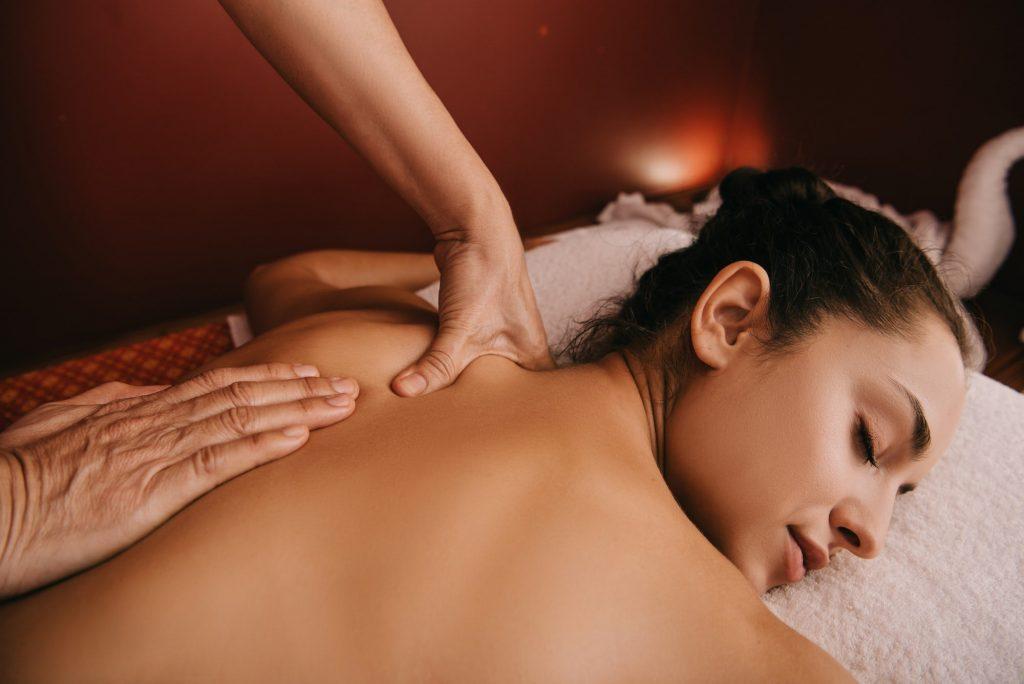 cropped view of masseur doing back massage to woman on massage mat